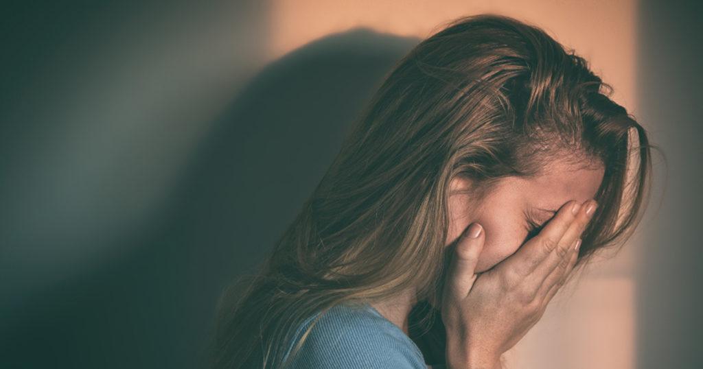 upset girl with face between her hands