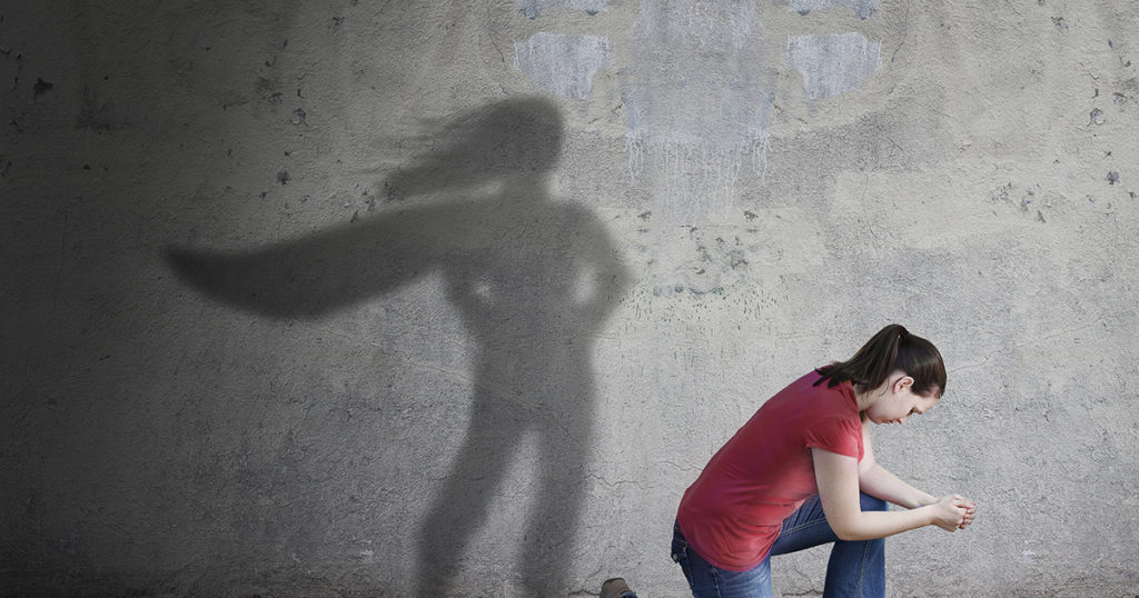 person kneeling in front of shadow with cape