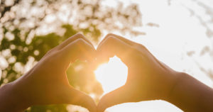 hands making heart sign against sun behind trees