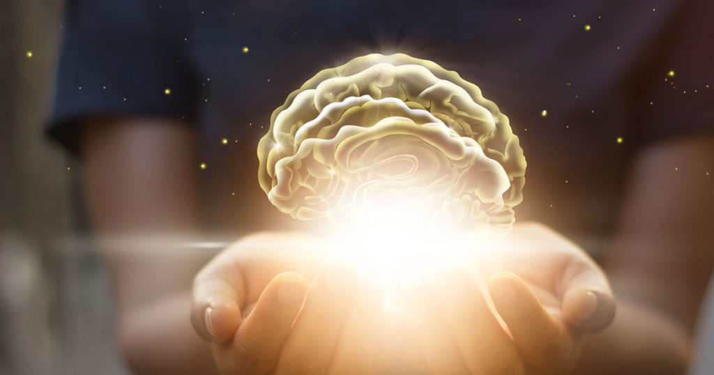 hands holding glowing brain