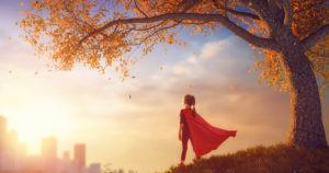 child in cape under tree