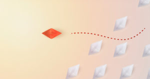 orange paper boat sailing away from fleet of white paper boats