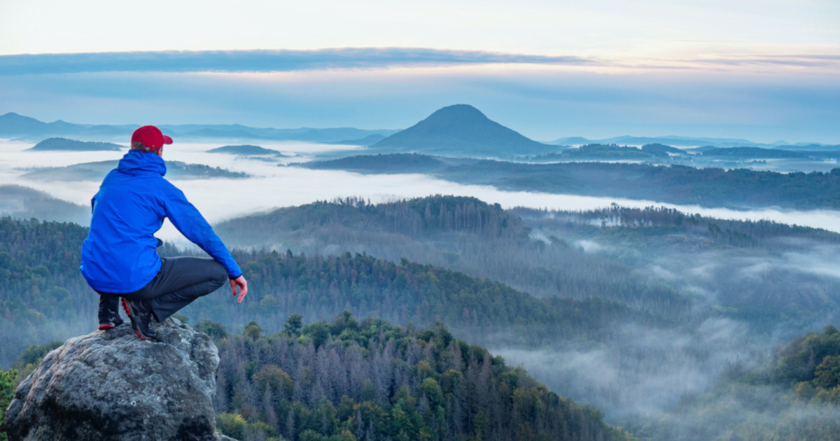 Man on sharp rocky edge, enjoy amazing birds view